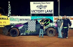 Crew Chief and the brains of the operation, six-year-old Landen Harris holds the checkered flag as his mom, Whitney Harris, and his driver dad, Branden Harris of Molino, FL, celebrate their fourth NeSmith/AR Bodies Street Stock Division win of the season on Saturday night at Flomaton Speedway in Flomaton, AL.  Branden Harris is second in the NeSmith/AR Bodies Street Stock Division point standings going into Week 13 of the 27-week 2015 season.  (Photo courtesy of Harris Racing)