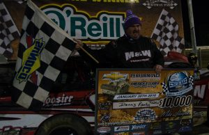 """Dennis """"Rambo"""" Franklin of Gaffney, SC holds the $10,000 check after winning the 100-lap 11th Annual World Championship Race for the NeSmith Chevrolet Dirt Late Model Series driving the M&W Transportation Special on Saturday night at Bubba Raceway Park in Ocala, FL.  Franklin had been trying for ten years to win the race, only to have something go wrong while leading.  The driver known as Rambo made a statement by leading 75 of the 100 laps and lapping all but the second and third-place cars.  He even held off a hard-charging Kyle Bronson of Brandon, FL in the last 11 laps of the race, after Bronson made a strategic move that should have left Franklin a sitting duck.  (NeSmith Media Photo by Bruce Carroll)"""